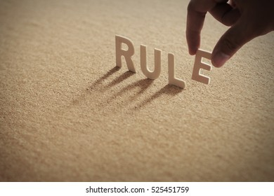 RULE wood word on compressed board with human's finger at E letter