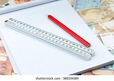 Ruler on a layer of bank notes with a pencil and a notebook