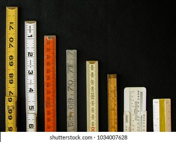 Rulers and scales in metric and inches descend along a chart or graph representing measurement, metrics, precision, decrease, accuracy and results with copy space.