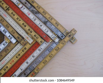 Rulers and scales in metric and inches form a chevron chart or graph representing accuracy, measurement, increase, growth and results with copy space.