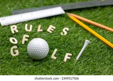 Rules of golf with golf ball and pencil on green grass.The rules of golf consist of a standard set of regulations and procedures by which the sport of golf should be played and prescribe penalties