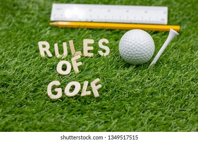Rules of golf with golf ball and pencil on green grass