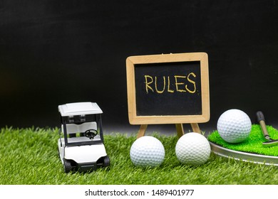 Rules of golf with golf cart and golf balls are on green grass