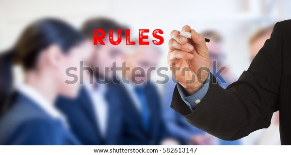 Rules, Male hand in business wear holding a thick pen, writing on an imaginary screen at the camera, business team in background, digital composing.