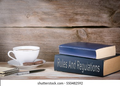 Rules And Regulations. Stack of books on wooden desk