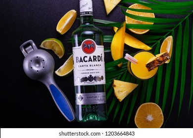rum bacardi on a black background with tropical fruits pineapple mango orange