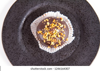 Rum ball decorated with chocolate and nuts on a black plate on a white background