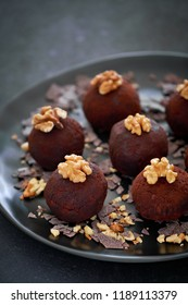 Rum balls are a truffle-like confection of sweet, dense cake flavored with chocolate and rum. Close-up on a dark plate of rum balls with wallnutsion dark background