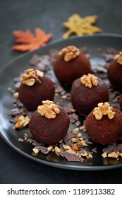 Rum balls are a truffle-like confection of sweet, dense cake flavored with chocolate and rum. Close-up on a dark plate of rum balls with wallnutsion dark background decorated with Autumn leaves.