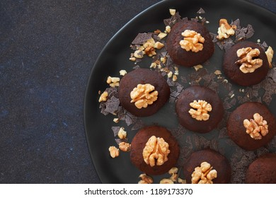 Rum balls are a truffle-like confection of sweet, dense cake flavored with chocolate and rum. Flat lay of dark plate of rum balls with wallnuts on dark background.
