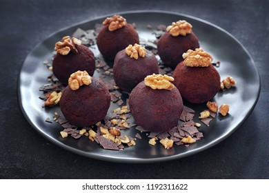 Rum balls are a truffle-like confection of sweet, dense cake flavored with chocolate and rum. It is a popular winter treat. Close-up on a dark plate of rum balls decorated with wallnuts.