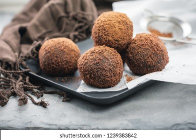 rum chocolate balls with cocoa powder on a tray.