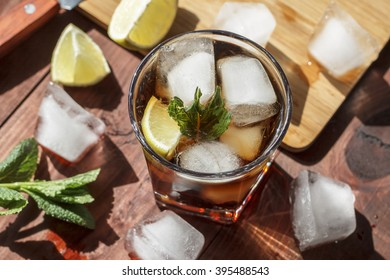 rum cocktail in a glass with ice, lime, mint, bread on a wooden table,  brandy, cuba Libre