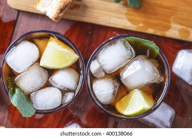 rum cocktail in a glass with ice, lime, mint, bread on a wooden table