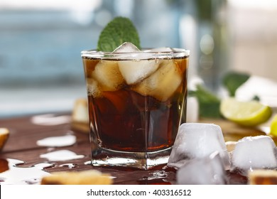 rum cocktail in a glass with ice, lime, mint, bread on a wooden table. flat position, top view, closeup