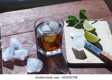 rum cocktail in a glass with ice, lime, mint, bread on a wooden table, brandy