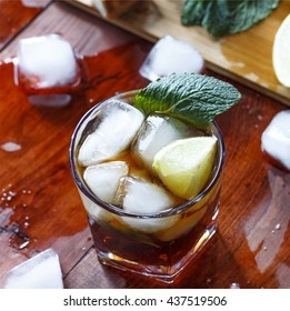 rum cocktail in a glass with ice, lime, mint, bread on a wooden table, brandy. Flat position, top view, closeup