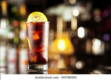 Rum cola casual cocktail with ice cubes and lemon at festive bar stand background.