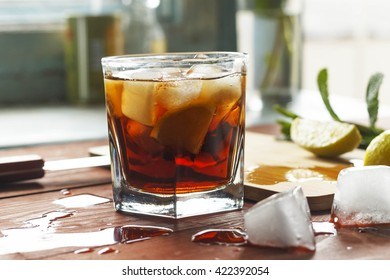 rum and cola with lime and Ice into the glass beaker closeup