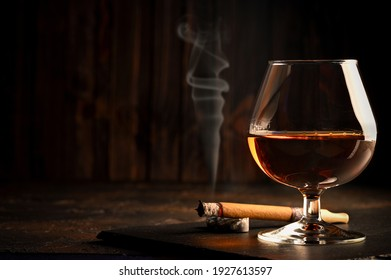 Rum in glasses with a bottle of rum and a cigar in the background. Black background