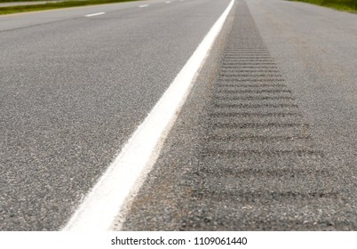 The rumble strip on the side of a highway, The strip consists of shallow pits in the paved shoulder that vibrate a vehicle if it crosses the line onto the shoulder.