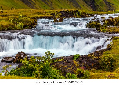 Rumbling cascading waterfall in Iceland. Wide picturesque valley along highway number one around the island. Travel in Iceland. Concept of active and extreme tourism