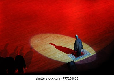 Rumi standing on peace of rug under spot light