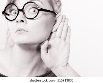 Rumors and gossips concept. Newsmonger girl making listening gesture. Shocked surprised gossiping woman. Gossip and chatter.