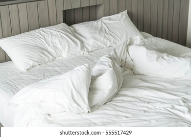 rumpled bed with white messy pillow decoration in bedroom interior