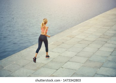 Run, baby, run Back view of young and active blonde woman in sports clothing running along the riverbank in the morning