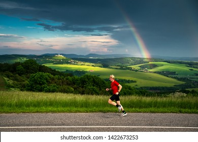 Run in beautiful nature, man train in summer green landscape after rain, rainbow and rural scenery in background