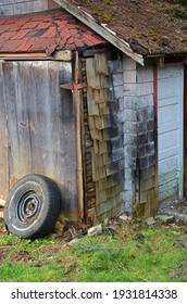 Run down decrepit garage with door and old car tire leaning on wall.