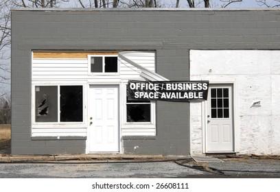 A run down, unkempt concrete building advertises office space for rent.