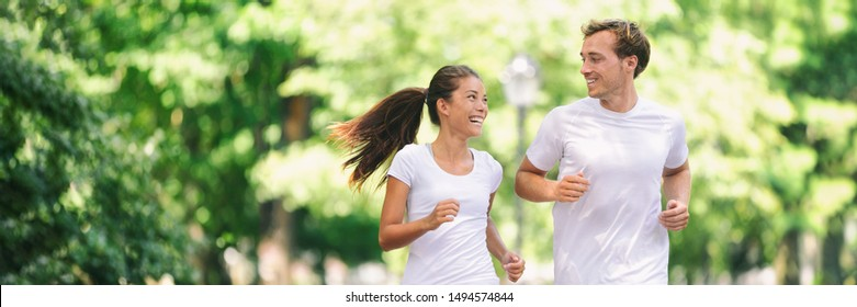 Run exercise fitness friends walking running talking together on fun race in city park panoramic banner background. Healthy active lifestyle young people, Asian woman, Caucasian man couple.