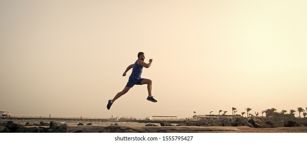 Run hard or walk home. Running man on beach. Runner training outdoors. Fit male sport fitness exercising in summer. Running sport and hobby. Daily workout great result. Man professional fitness coach.