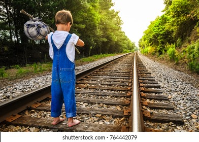 A runaway boy standing on a train track looking down