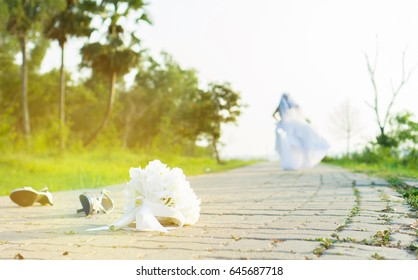 Runaway bride. Wedding day.bride leave bouquet and shoes on road runaway