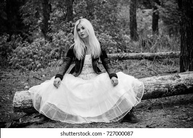 A runaway bride in a wedding dress and a leather jacket in the forest. Difficulties at the wedding. Fashionable girl in grunge style