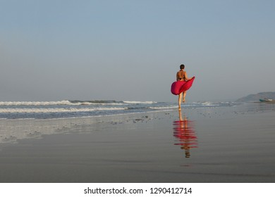 runaway girl. girl in a red dress runs along the seashore. red dress reflected in sea water