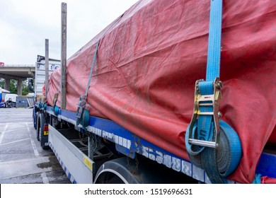 Runcorn, Cheshire / UK - October 01 2019: Illustrative Editorial,WS Transportation Scania Side View of a Red  Sheeted Load of Steel Tubing Close Up showing Ratchet Straps and Metal Posts..