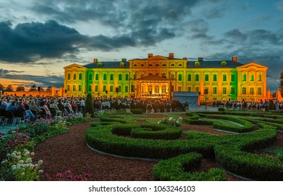 Rundale palace, Latvia - July 11, 2015: People are sitting and hearing an old classical music being out-of-door in summer floral park of the governmental museum of ancient Rundale palace