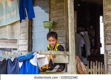 Rundum, Sabah, Malaysia - 11 February 2013: A Murut boy at his parents' decent wooden house at Kg Rundum, a secluded village in the mountain region of the Interior. Some laundry hanging for drying.