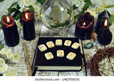 Rune and black candles, magic crystal and pentagram on witch altar. Esoteric, gothic and occult concept, Halloween mystic background, divination ritual