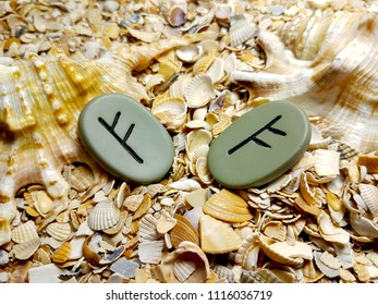 Rune Fehu Feoh Fe, symbol of money, wealth, prosperity. Magic stone on the beach in the sand.