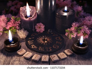 Runes, black candles and zodiac circle against the background with sakura flowers. Occult, esoteric and divination still life. Halloween background with vintage objects