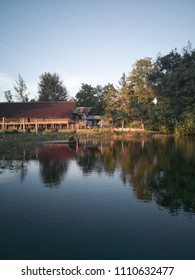 Rungus traditional longhouse at Tindakon Dazang Beach Resort Kudat Sabah with reflection in water. mangrove tree.