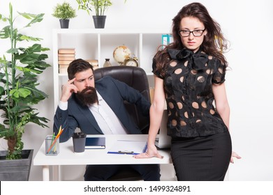 Runing office successfully. Office employees. Company owner and office secretary. Sexy woman and bearded man in office wear. Sensual female assistant standing at boss desk.