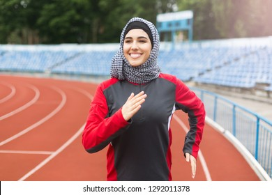 Runner arabian girl wearing hijab on stadium. Modern muslim woman concept