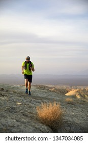 Runner athlete with backpack running on the wild trail at red mountains in the desert
