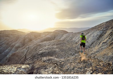 Runner athlete with backpack running on the wild mountains in the desert at sunset